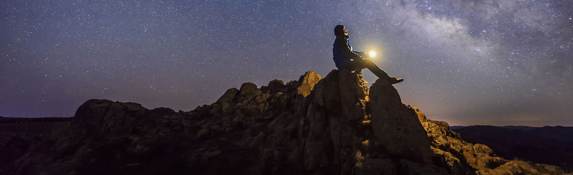 Man sitting under The Milky Way Galaxy with light on his hands. - Who Are You by Jerald Simon - published by Music Motivation